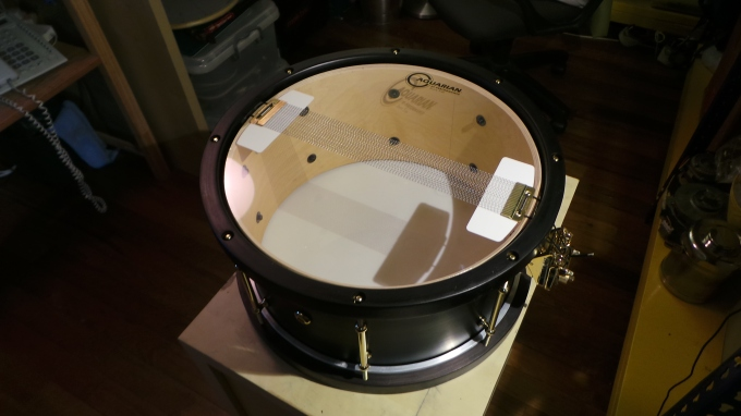 Pantheon Percussion: Satin Black 10-ply 14 x 7 Maple snare with wooden hoops and Gold hardware